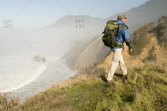 A man hiking on foggy bluff at Sinkyone State Park, Lost Coast, California.
