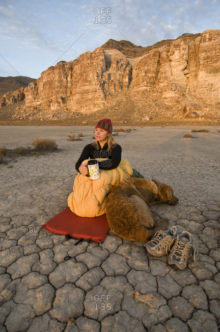 A woman and her dog camped on a dry, cracked lake bed, Delta, Utah.