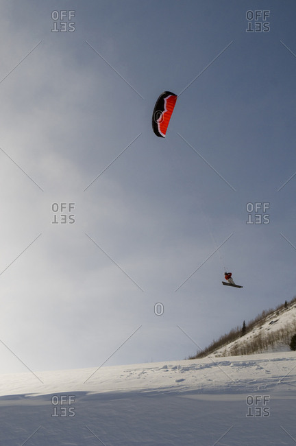 A man flying high above the ground while kite skiing on Shriners Hill in Silverton, Colorado.