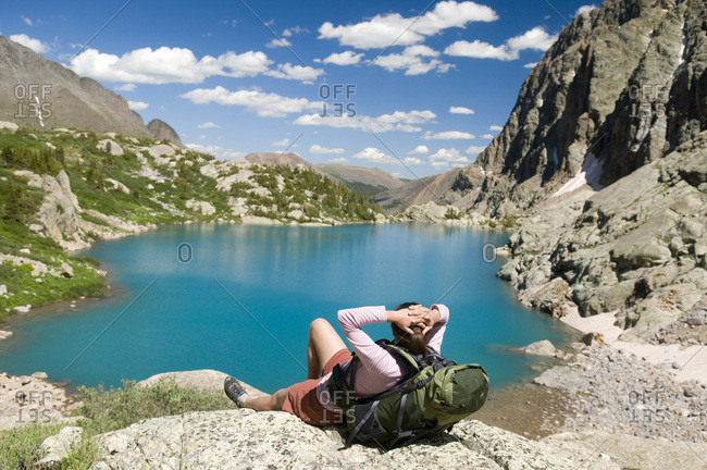 A woman hiker rests next to turquoise lake, Weminuche Wilderness, Colorado.