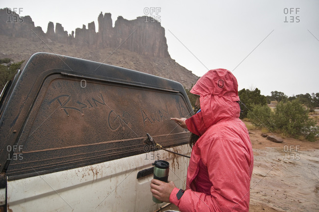 "A woman writes, ""Rain go away"" on a dusty truck window during a rainstorm, Indian Creek, Monticello, Utah."