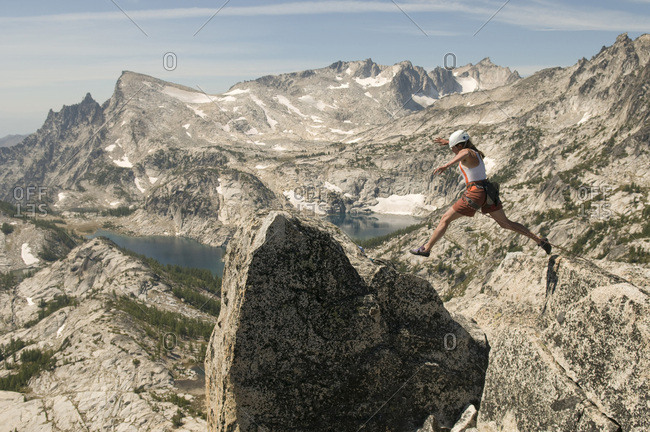 A woman jumping onto a summit in the Enchantment Peaks, Alpine Lakes Wilderness, Leavenworth, Washington.