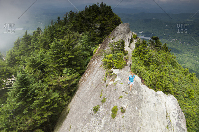 A woman trail running along a rocky ridge in Grandfather Mountain State Park, Linville, North Carolina.