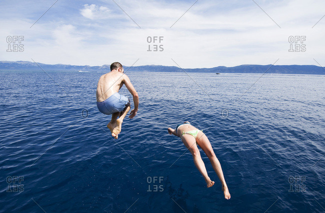 A young couple dive in the crystal blue water on a hot summer day in Lake Tahoe, Nevada.