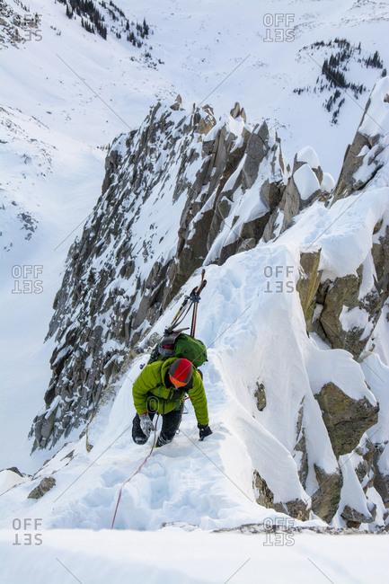 A man alpine climbing a ridgeline in Little Cottonwood Canyon, Salt Lake City, Utah.