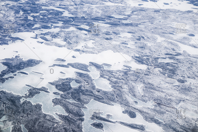 An aerial landscape of frozen lakes over the rocky tundra of the arctic in Greenland.