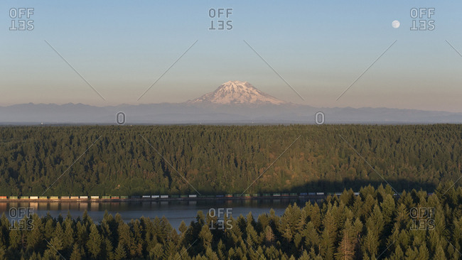 A train runs next to Puget Sound in front of Mount Rainier and a full moon through the forest.