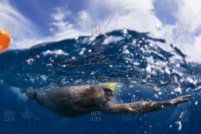 Underwater view of a swimmer rounding a buoy during an annual ocean swimming race in the tropical waters off of Mana Island, Fiji.