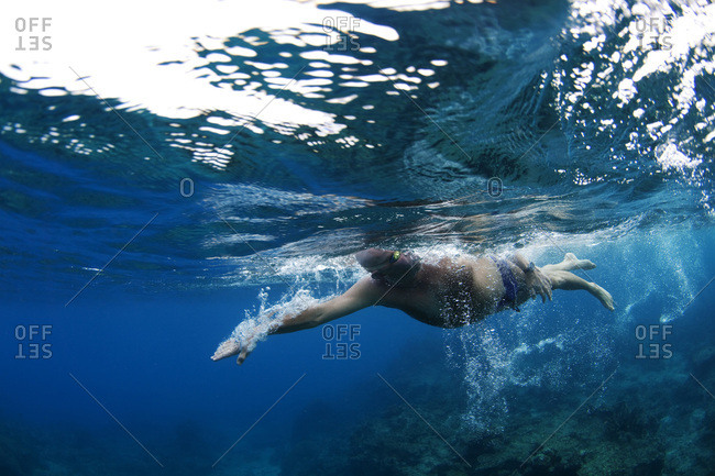Underwater view of a swimmer enjoying a relaxing swim in the tropical waters off of Mana Island, Fiji.