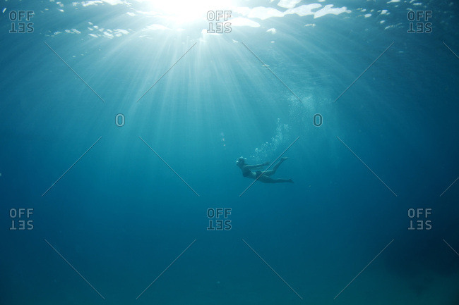 Underwater view of a woman swimming through rays of sun leaving a trail of bubbles in the tropical waters off of Mana Island, Fiji.