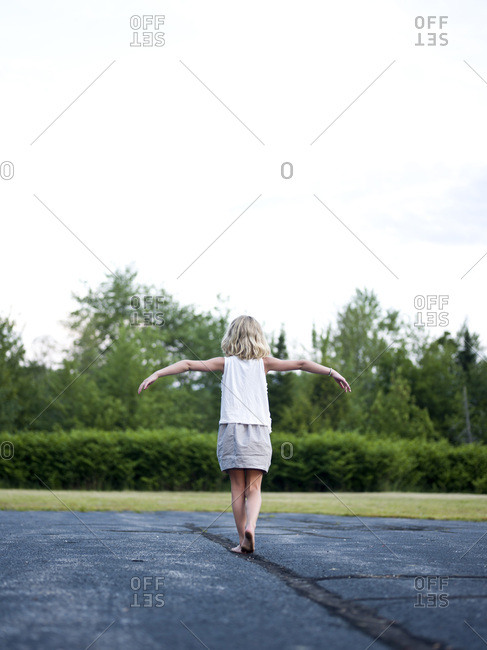 a girl walks a straight line on a paved surface