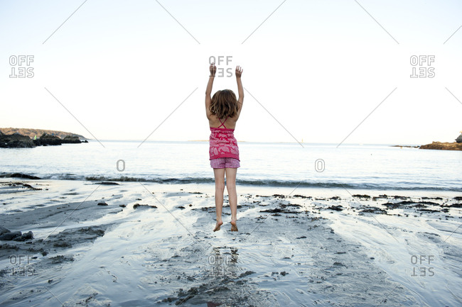 a girl jumps in the air at the beach in southern maine