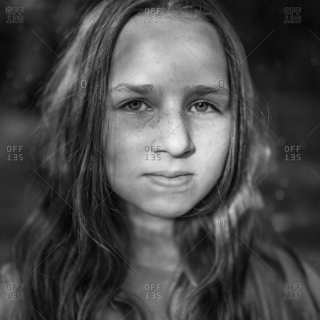 Portrait of a young girl with freckles in black and white