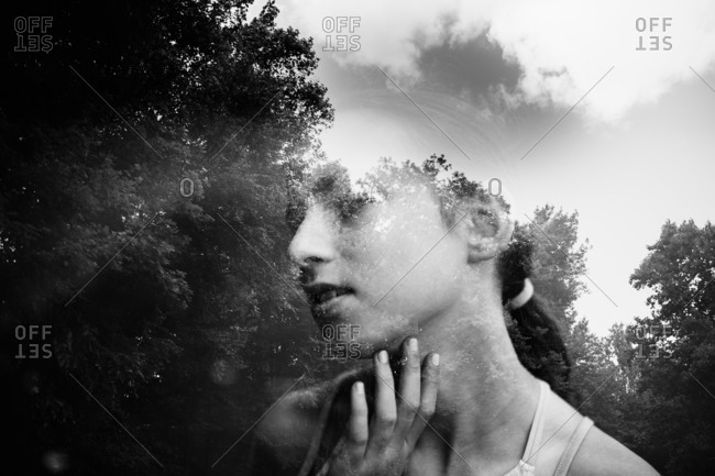 Double exposure of girl and trees and sky in black and white