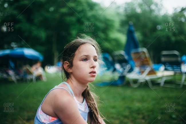 Girl looking away while sitting by lounge chairs at pool