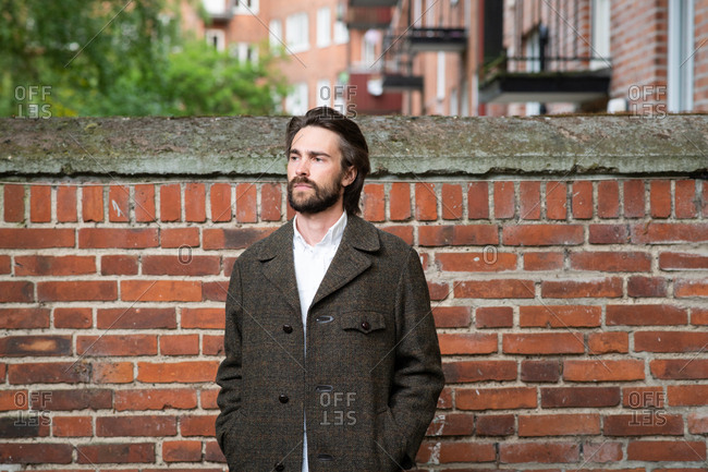 Handsome brunette man with beard standing by brick wall