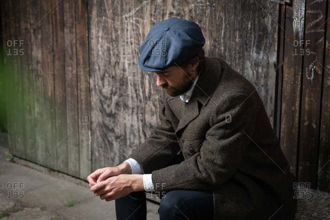 Man with beard wearing hat sitting and thinking