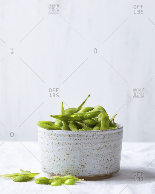 Edamame beans in speckled ceramic bowl on light background