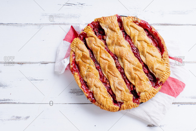 Rhubarb strawberry pie decorated with braided lattice on white wood table