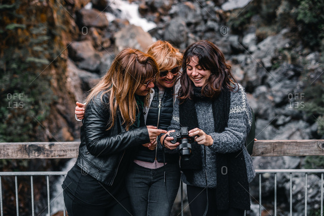 Happy women standing by waterfall near Lake Matherson in New Zealand and watching photos on digital camera