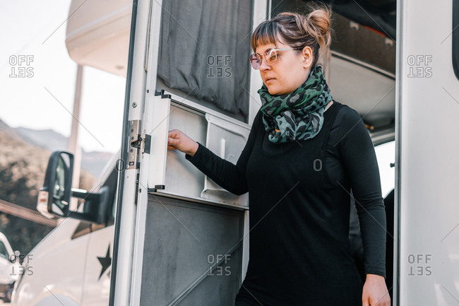 Young woman standing by open door of camper van near Lake Matherson in New Zealand on sunny day