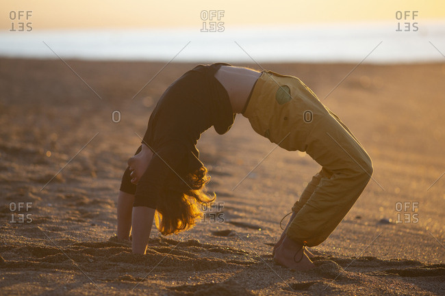 Sportive man in yellow pants barefoot performing yoga meditation workout on sand beach in sunset evening