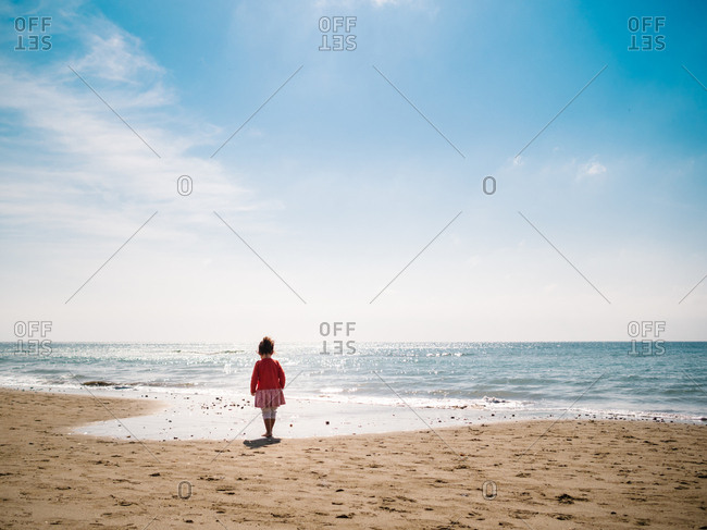 Back view of female toddler walking on sandy seaside on background of calm water