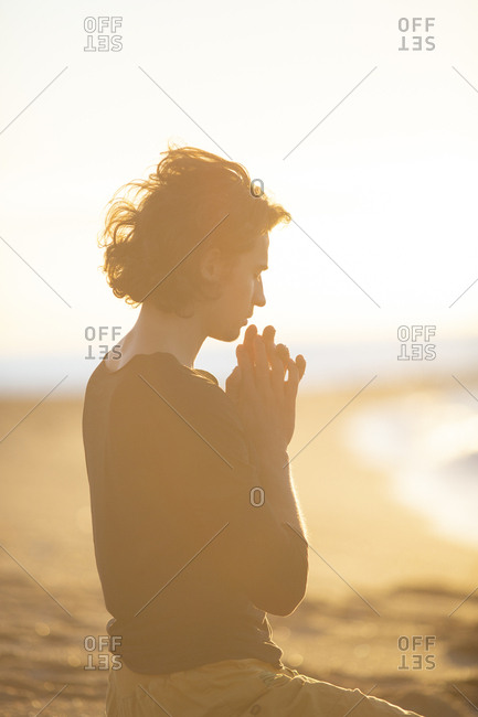 Side view of man concentrating on thoughts with closed eyes and hands in prayer gesture sitting on knees on sandy beach in sunlight