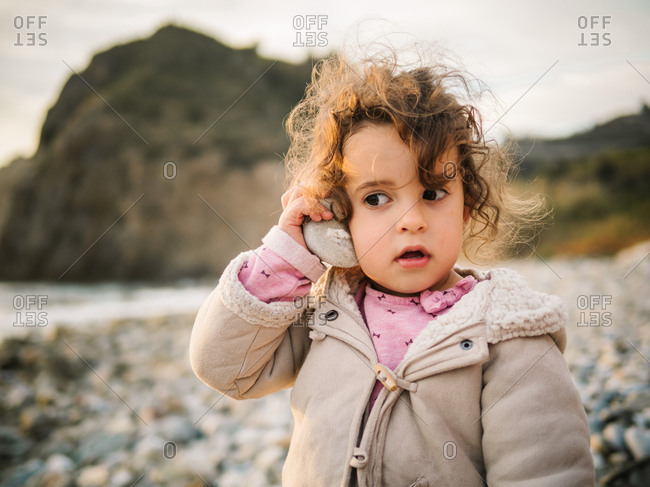 Portrait of cute female kid listening to conch with rapt attention while resting on stony seaside
