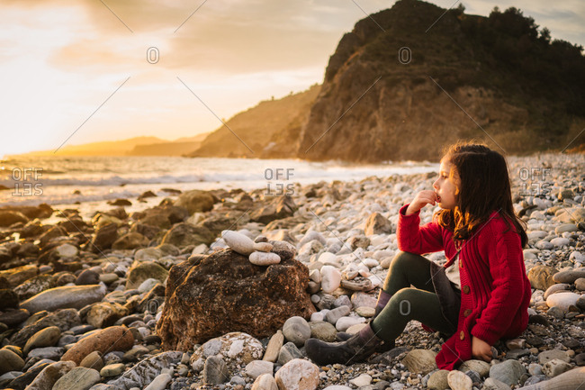 Side view of pensive female kid sitting on stony beach and admiring sundown on background of calm seaside