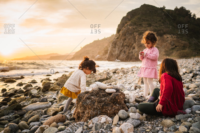 Toddler female twins playing on stony seashore on background of calm water