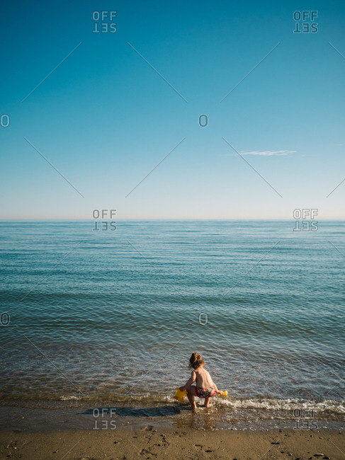 Back view of anonymous cute female toddler playing on sandy shore on background of calm sea