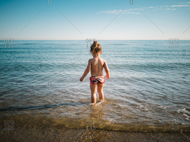 Back view of anonymous adorable toddler girl in swimming suit standing in warm water of calm sea