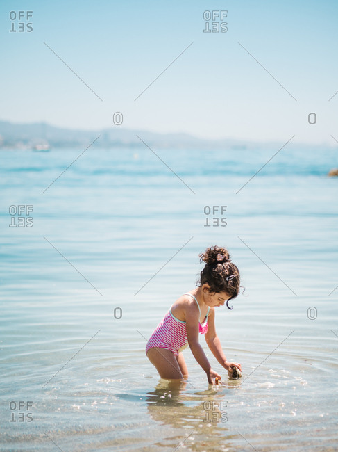 Side view of adorable toddler girl in swimming suit standing in warm water of calm sea