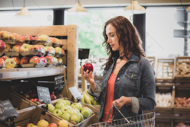 Female shopper buying apples in a grocery store