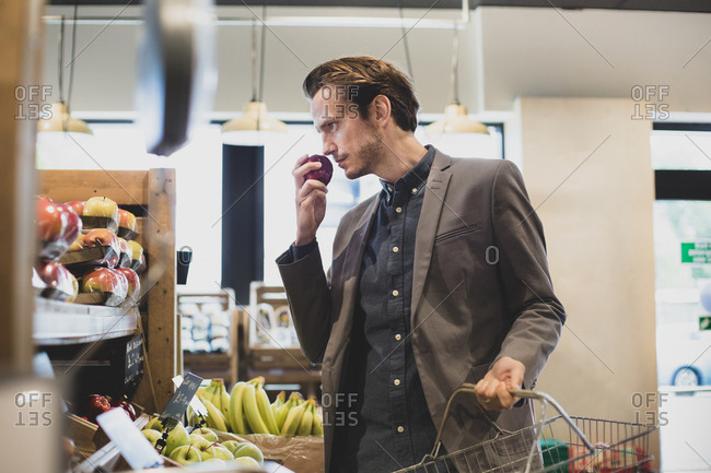Male shopper buying apples in a grocery store