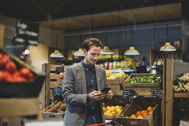 Adult male late night grocery shopping and using smartphone