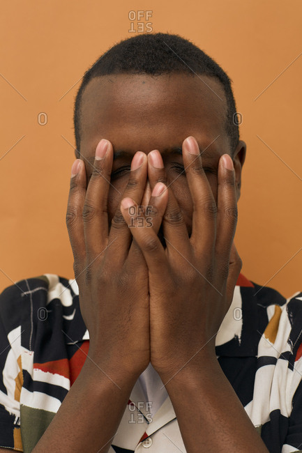 Unrecognizable African man hiding his face in his hands