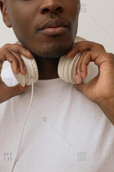 Stylish Black man with headphones wearing white T-shirt