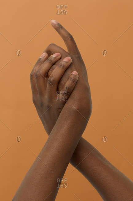 Male hands twisted together on light brown background