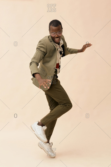 Handsome African American guy wearing stylish outfit dancing studio full shot