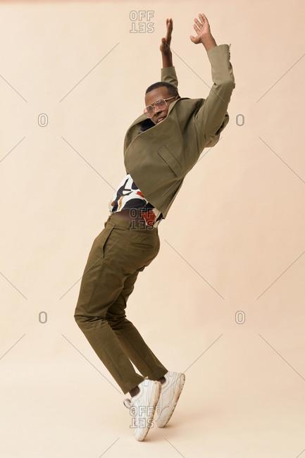 Joyful African American guy wearing stylish outfit dancing