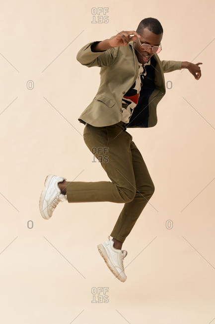 Young dandy wearing stylish outfit jumping high full shot