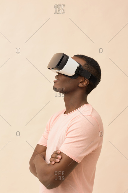 Side view waist up portrait of Black male model wearing VR glasses