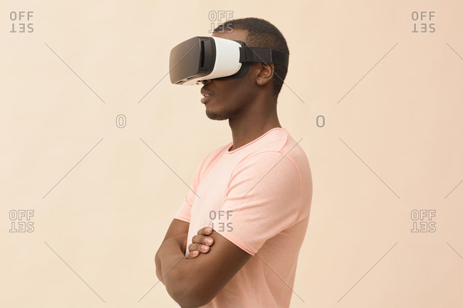 Side view portrait of concentrated young man wearing VR headset