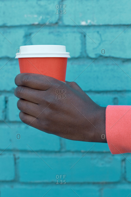 Hand of man wearing coral sweatshirt with coral take away cup against turquoise blue brick wall