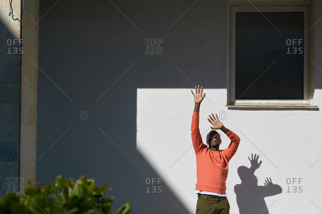 Young man wearing coral sweatshirt raising hands standing against white building