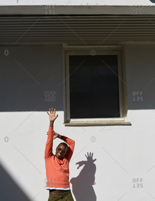 African American man stretching himself standing against white building