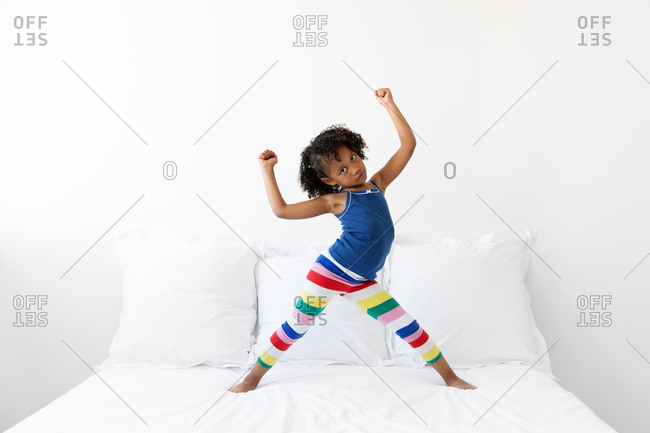 Energetic little girl dancing on white bed