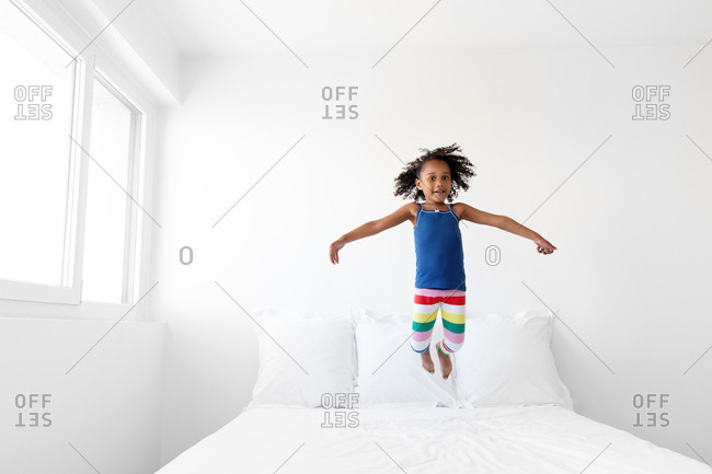 Young girl with afro hair jumping on bed